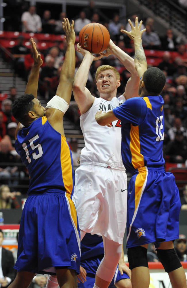 San Diego State's James Johnson (12) shoots between  San Jose State's Chris Cunningham (15) and Jalen James (12) during the second half of an NCAA college basketball game on Tuesday, Feb. 25, 2014, in San Diego