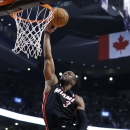Miami Heat's Dwyane Wade (3) goes to the basket past Toronto Raptors' Jonas Valanciunas, left, during the first half of an NBA basketball game in Toronto, Friday, Nov. 29, 2013 The Associated Press