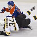 Boston Bruins' Carl Soderberg (34) is checked by Edmonton Oilers' Nick Schultz (15) during the second period of an NHL hockey game, Thursday, Dec. 12, 2013 in Edmonton, Alberta. (AP Photo/The Canadian Press, Jason Franson)