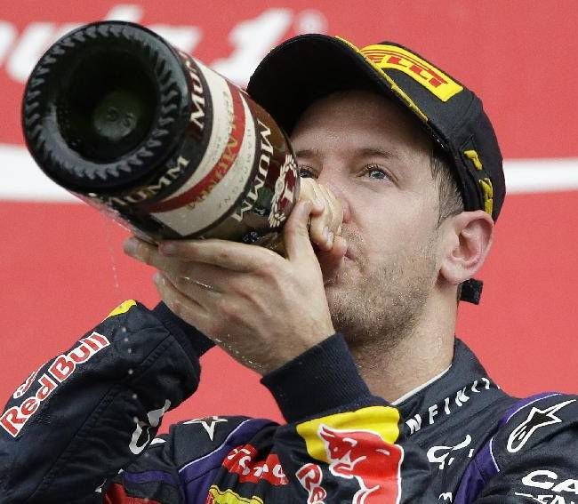Red Bull driver Sebastian Vettel of Germany drinks champagne as he celebrates his win in the Korean Formula One Grand Prix at the Korean International Circuit in Yeongam, South Korea, Sunday, Oct. 6, 2013