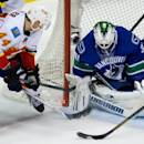 Vancouver Canucks goalie Eddie Lack, right, of Sweden, stops Calgary Flames' Chris Butler during second period NHL hockey action in Vancouver, British Columbia, on Saturday March 8, 2014. (AP Photo/The Canadian Press, Darryl Dyck)
