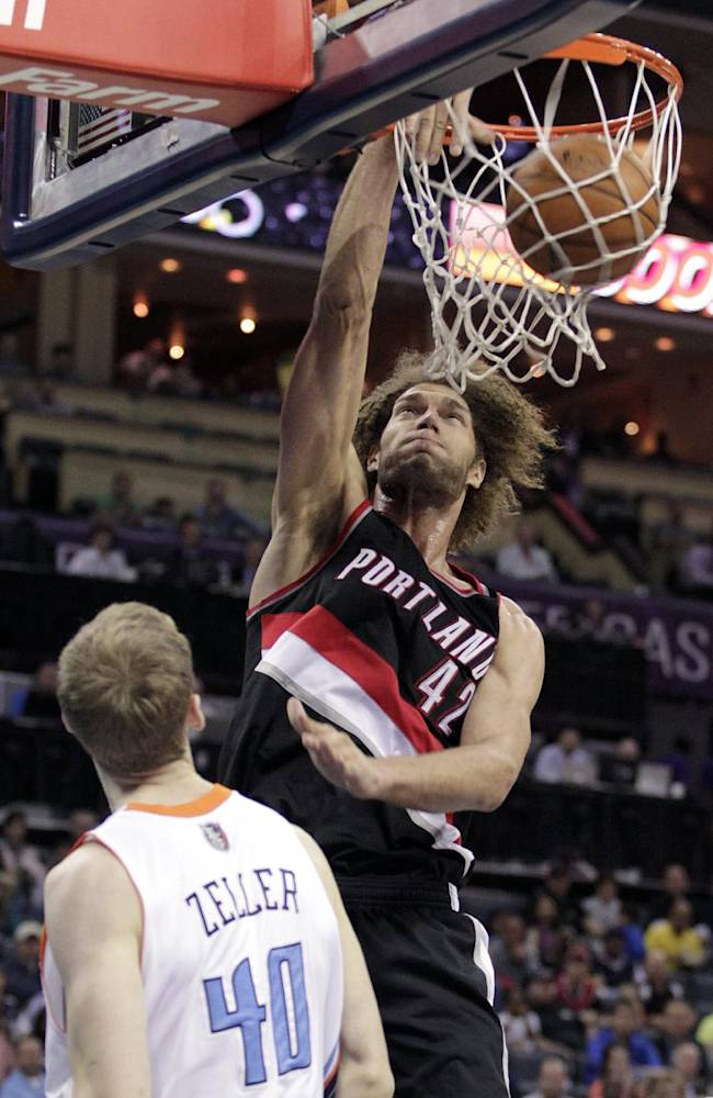 Portland Trail Blazers' Robin Lopez (42) dunks over Charlotte Bobcats' Cody Zeller (40) during the second half of an NBA basketball game in Charlotte, N.C., Saturday, March 22, 2014. The Bobcats won 124-94