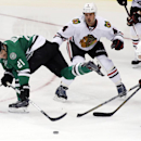 Dallas Stars left wing Antoine Roussel (21), of France, tries to get the puck past Chicago Blackhawks defenseman Niklas Hjalmarsson (4), of Sweden, center Jonathan Toews (19) and defenseman Nick Leddy during the second period of an NHL hockey game Saturda