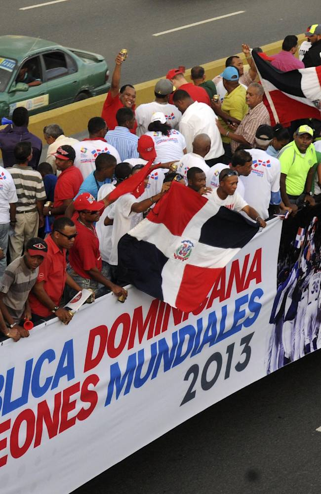 Dominican Republic baseball players and fans ride atop a truck during the 2013 World Baseball Classic victory celebration in Santo Domingo, Dominican Republic, Thursday, Nov. 28, 2013. The Dominican Republic team won the third edition of the World Baseball Classic in March, finishing unbeaten in eight games