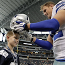 Dallas Cowboys tight end Jason Witten, right, puts his helmet on 12-year-old Michael Flynn, left, of Greensboro, N.C., as Witten talks to Flynn on the sideline during team warm ups before a NFL preseason football game, Thursday, Aug. 28. 2014, in Arlingto