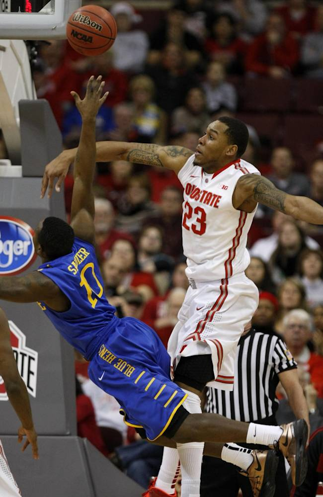 Ohio State's Amir Williams, right, fouls Delaware's Devon Saddler who goes up for a shot during the first half of an NCAA college basketball game in Columbus, Ohio, Wednesday, Dec. 18, 2013. ( AP Photo/Paul Vernon)