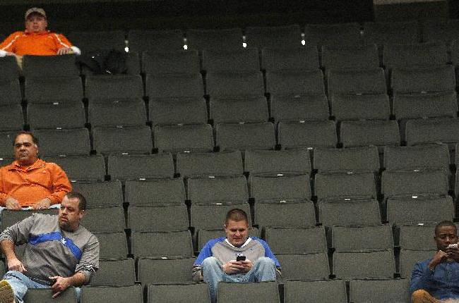 People sit in the stands during the first half of an NCAA college basketball game in the quarterfinal round of the Southeastern Conference tournament, Friday, March 14, 2014, in Atlanta