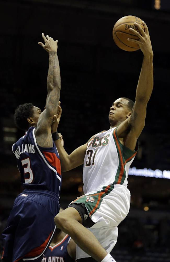 Milwaukee Bucks' John Henson (31) puts up a shot against Atlanta Hawks' Louis Williams (3) during the second half of an NBA basketball game Saturday, Jan. 25, 2014, in Milwaukee
