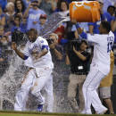 Kansas City Royals' Lorenzo Cain, left, tries to dodge a cooler of water being emptied by teammate Salvador Perez (13) following a baseball game against the Minnesota Twins at Kauffman Stadium in Kansas City, Mo., Friday, July 3, 2015. Cain scored the winning run. The Royals defeated the Twins 3-2 in 10 innings. (AP Photo/Orlin Wagner)