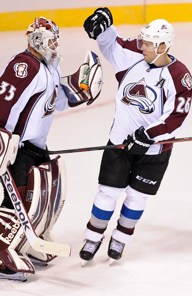 Colorado Avalanche goalie Jean-Sebastien Giguere celebrates with teammate Paul Stastny after an NHL preseason hockey game against the Los Angeles Kings, Saturday, Sept. 28, 2013, in Las Vegas. The Avalanche won 3-2