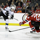 San Jose Sharks' Logan Couture (39) takes a shot past New Jersey Devils' Anton Volchenkov (28), of Russia, during the first period of an NHL hockey game Sunday, March. 2, 2014, in Newark, N.J The Associated Press