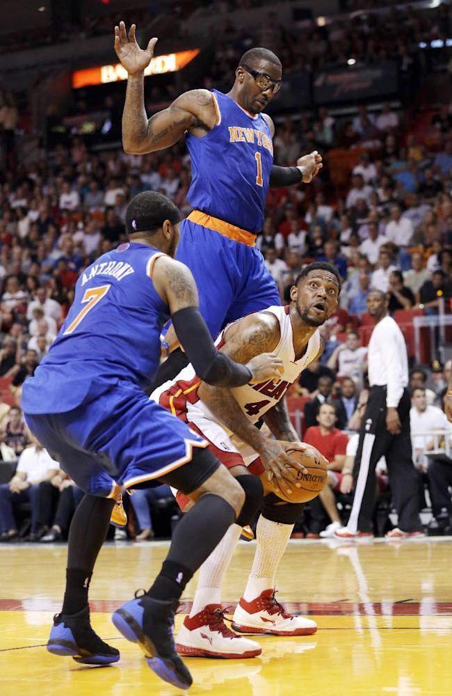 Miami Heat forward Udonis Haslem goes up for a shot against New York Knicks forward Carmelo Anthony (7) and forward Amar'e Stoudemire (1) during the first half of an NBA basketball game, Sunday, April 6, 2014, in Miami