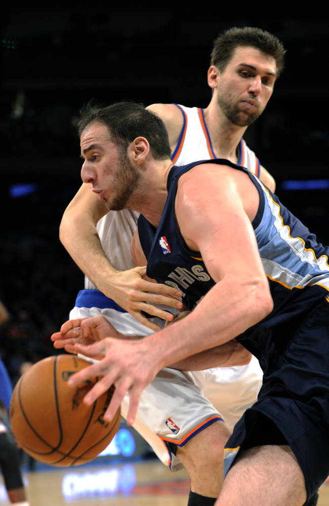 Memphis Grizzlies' Kosta Koufos, left, drives to the basket past New York Knicks' Andrea Bargnani, of Italy, during the fourth quarter of an NBA basketball game Saturday, Dec. 21, 2013, at Madison Square Garden in New York. The Grizzlies defeated the Knicks 95-87