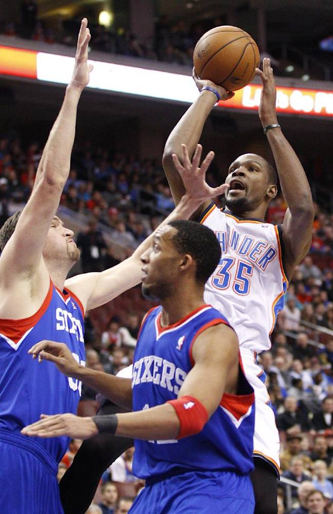 Oklahoma City Thunder's Kevin Durant, right, shoots as Philadelphia 76ers' Spencer Hawes, left, and Evan Turner defend during the first half of an NBA basketball game, Saturday, Jan. 25, 2014, in Philadelphia