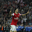 Arsenal's Mikel Arteta celebrates after scoring in a penalty shoot-out against Wigan Athletic during their English FA Cup semifinal soccer match at Wembley Stadium in London, Saturday, April 12, 2014