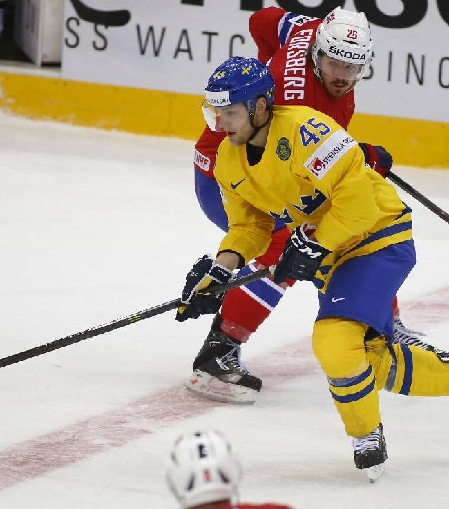 Norway's Kristian Forsberg, right, and Sweden's Oscar Moller battle for the puck during the Group A preliminary round match at the Ice Hockey World Championship in Minsk, Belarus, Tuesday, May 13, 2014