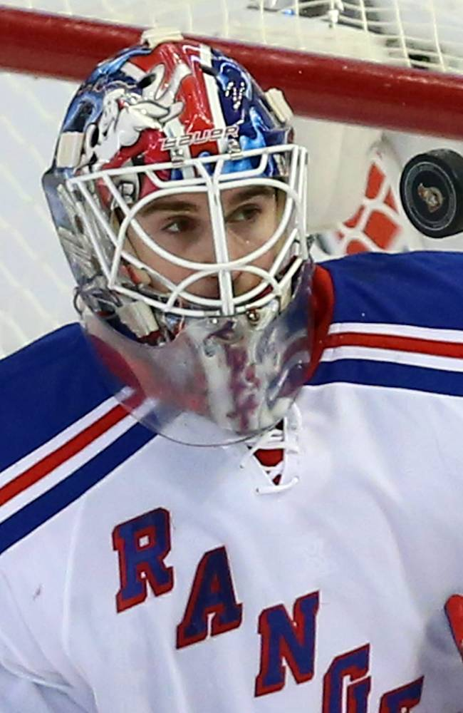 New York Rangers goaltender Cam Talbot (33) keeps his eyes on a flying puck during the second period of an NHL hockey game against the Ottawa Senators in Ottawa, Saturday, Jan. 18, 2014