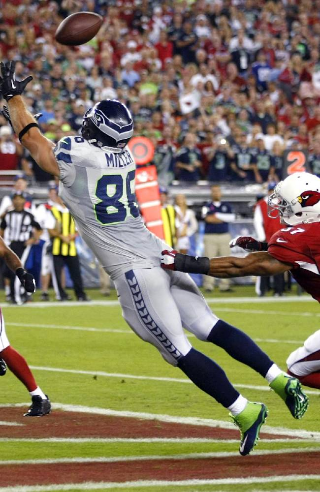 Seattle Seahawks tight end Zach Miller (86) pulls in a touchdown pass as Arizona Cardinals strong safety Yeremiah Bell (37) and Rashad Johnson (26) defend during the first half of an NFL football game, Thursday, Oct. 17, 2013, in Glendale, Ariz