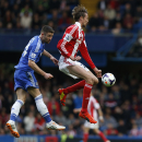 Chelsea's Gary Cahill, left, competes with Stoke City's Peter Crouch during their English Premier League soccer match at Stamford Bridge, London, Saturday, April 5, 2014