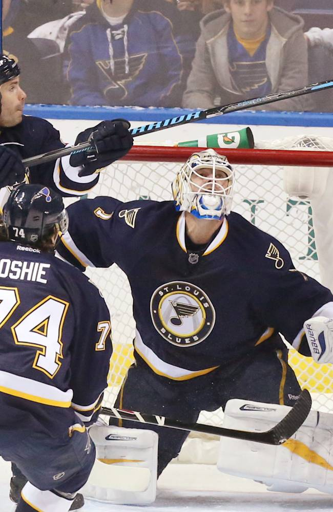 St. Louis Blues defenseman Barret Jackman deflects the puck over goaltender Brian Elliott in first period action during a game between the St. Louis Blues and the Dallas Stars on Saturday, Nov. 23, 2013, in St. Louis