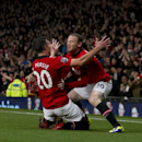Manchester United s Robin van Persie, left, celebrates with teammate Wayne Rooney after scoring against Arsenal during their English Premier League soccer match at Old Trafford Stadium, Manchester, England, Saturday Nov. 10, 2013