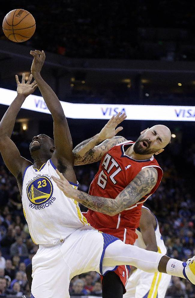 Golden State Warriors' Draymond Green (23) and Atlanta Hawks' Pero Antic (6) fight for a rebound during the second half of an NBA basketball game Friday, March 7, 2014, in Oakland, Calif