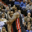 Miami Heat forward LeBron James, right, hugs guard Norris Cole, left, during the second quarter of an NBA basketball game against the Minnesota Timberwolves in Minneapolis, Saturday, Dec. 7, 2013. James had a game-high 21 points as the Heat won 103-82 The