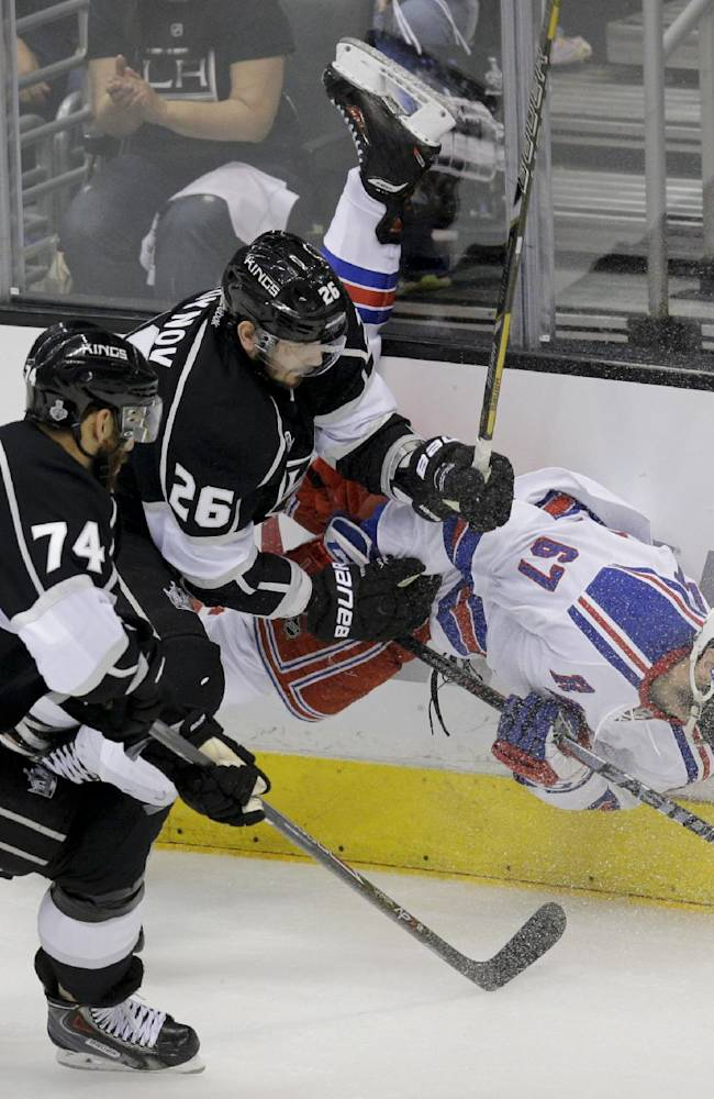 New York Rangers left wing Benoit Pouliot, right, is checked by Los Angeles Kings defenseman Slava Voynov, of Russia, middle, as left wing Dwight King looks on during the third period of Game 2 in the NHL hockey Stanley Cup Finals in Los Angeles, Saturday, June 7, 2014