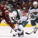 Minnesota Wild's Jason Zucker (16) tries to control the puck as Arizona Coyotes' Martin Hanzal (11), of the Czech Republic, takes a jab at the puck with his stick and Wild's Stu Bickel (4) moves in to help out during the second period of an NHL hockey gam