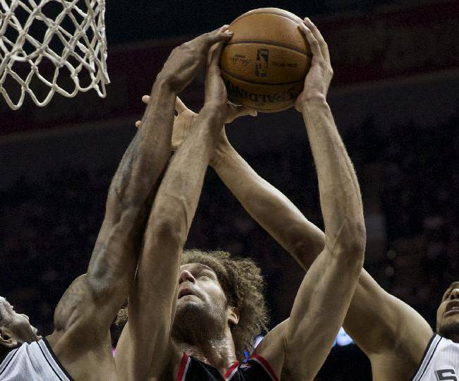 Portland Trail Blazers center Robin Lopez, center, grabs a rebound during Game 2 of a Western Conference semifinal NBA basketball playoff series against the San Antonio Spurs, Thursday, May 8, 2014, in San Antonio. San Antonio won 114-97