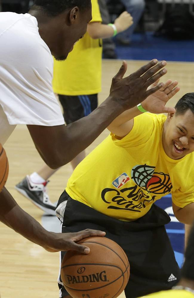 An Indiana Pacers player exchanges high-fives with a Filipino Special Olympics athlete during their basketball clinic Wednesday, Oct. 9, 2013, at the Mall of Asia Arena at suburban Pasay city, south of Manila, Philippines. The Indiana Pacers will play against the Houston Rockets on Thursday in the first NBA game in this basketball-obsessed Southeast Asian nation, part of the NBA's global schedule that will have eight teams play in six countries this month