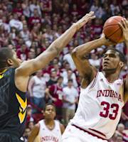 Indiana's Jeremy Hollowell (33) puts up a shot over the defense of Iowa's Melsahn Basabe (1) in the second half of an NCAA college basketball game, Thursday, Feb. 27, 2014, in Bloomington, Ind. Indiana defeated Iowa 93-86. (AP Photo/Doug McSchooler)