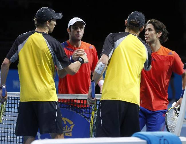 David Marrero of Spain, second left, and Fernando Verdasco of Spain, right, shake hands after defeating Bob Bryan and Mike Bryan of the United States in the final of the ATP World Tour Finals doubles tennis match at the O2 Arena in London Monday, Nov. 11, 2013