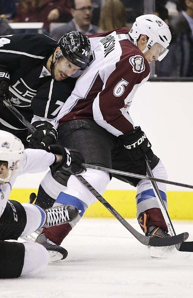 Los Angeles Kings' Dwight King, left, fights for the puck with Colorado Avalanche's Erik Johnson, right, and Nathan MacKinnon during the second period of an NHL hockey game on Saturday, Nov. 23, 2013, in Los Angeles