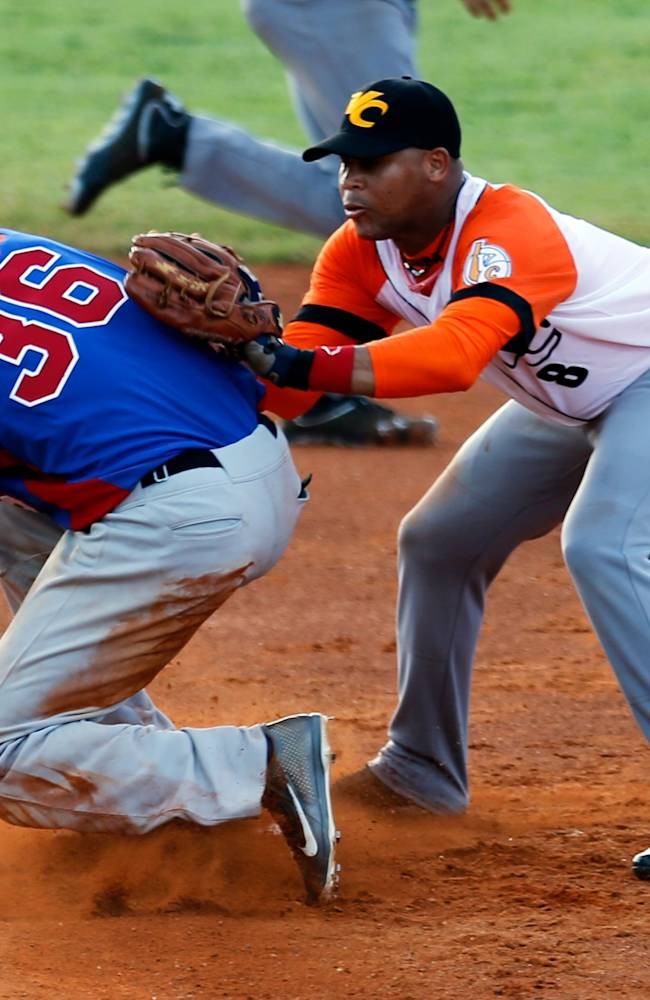 Dominican Republic's infielder Hector Gomez, left, slides onto second base as Cuba's infielder Jose Miguel Fernandez attempts to tag him out during a Caribbean Series baseball game in Porlamar, Venezuela, Monday, Feb. 3, 2014