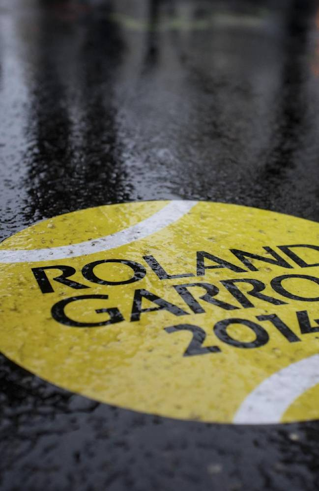 A rain-covered sticker of a tennis ball shows the way to walk towards the French Open tennis tournament outside the Roland Garros stadium, in Paris, France, Monday, May 26, 2014. A light drizzle is expected top cause delays in the first round matches