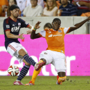 New England Revolution midfielder Lee Nguyen (24) battles against Houston Dynamo defender Kofi Sarkodie (8) during the first half of an MLS soccer match at BBVA Compass Stadium, Thursday, Oct. 16, 2014, in Houston The Associated Press