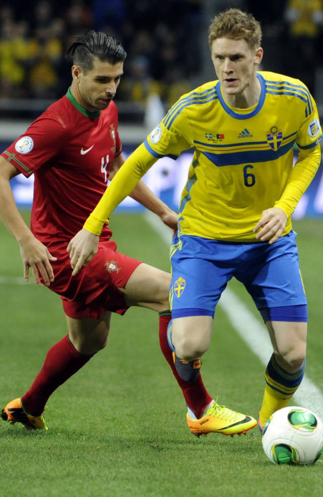Porgutal's Miguel Veloso, left, fights for the ball with Sweden's Rasmul Elm during their World Cup 2014 qualifying playoff second leg soccer match between Sweden and Portugal at Friends Arena in Stockholm, Tuesday, Nov. 19, 2013.  (AP/TT/Erik Martensson)  SWEDEN OUT