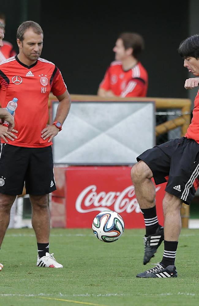 German national soccer team head coach Joachim Loew, right, kicks a ball besides assistant coach Hansi Flick, center, and goalkeeper coach Andreas Koepke during a training session in Santo Andre near Porto Seguro, Brazil, Thursday, July 10, 2014. Germany faces Argentina on upcoming Sunday in Maracana Stadium in Rio de Janeiro, in the final of the World Cup