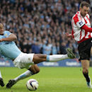 Sunderland's Steven Fletcher, right, has a shot on goal, blocked by Manchester City's Vincent Kompany during their English League Cup Final at Wembley Stadium, London Sunday March 2, 2014. City won the final 3-1