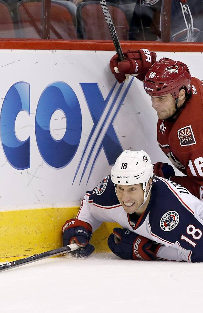 Columbus Blue Jackets' R.J. Umberger (18) reaches out for the puck after being checked into the boards by Phoenix Coyotes' Rostislav Klesla (16), of the Czech Republic, during the first period of an NHL hockey game Thursday, Jan. 2, 2014, in Glendale, Ariz