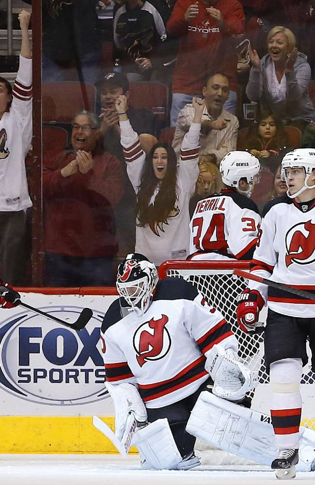 As Coyotes fans cheer for a goal by Phoenix Coyotes' Jordan Szwarz, New Jersey Devils' Patrik Elias (26), of the Czech Republic, Jon Merrill (34), Anton Volchenkov, right, of Russia, and goalie Martin Brodeur react during the first period of an NHL hockey game on Saturday, Jan. 18, 2014, in Glendale, Ariz