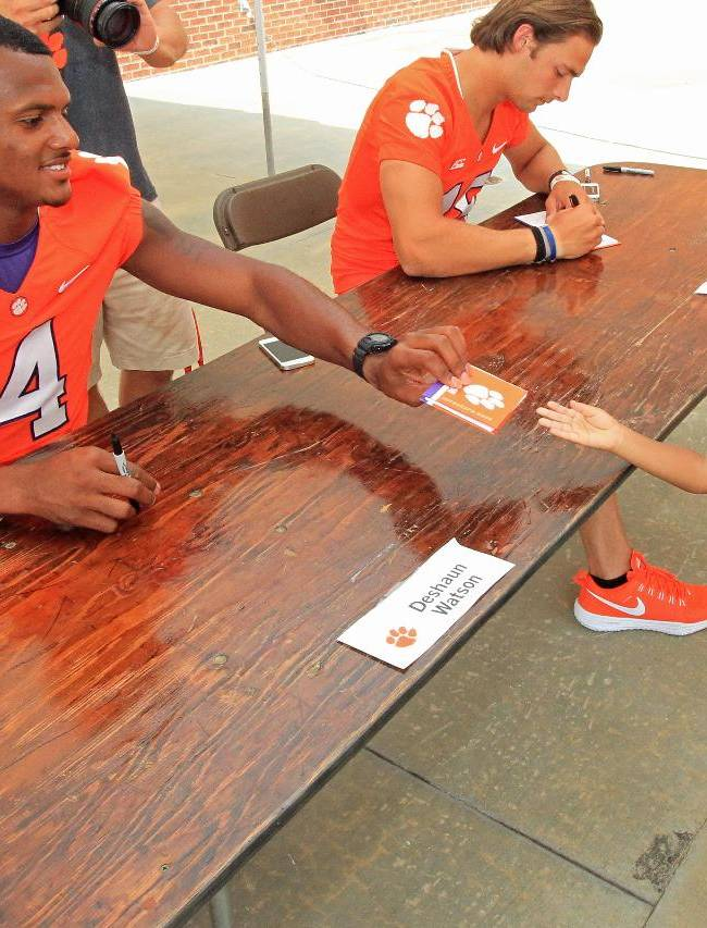Clemson NCAA college football quarterback Deshaun Waton, left, hands an autograph book back to a young fan at the Tigers' Fan Appreciation Day at Memorial Stadium in Clemson, S.C. on Sunday, Aug, 17, 2014