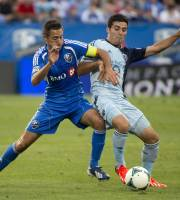 Montreal Impact's Davy Arnaud, left, and Sporting Kansas City's Soony Saad battle for the ball during the first half of their MLS soccer game in Montreal, Saturday, July 27, 2013. (AP Photo/The Canadian Press, Graham Hughes)