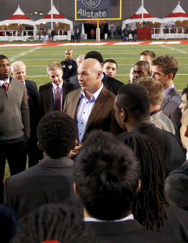 Former New Mexico and Chicago Bears football player Brian Urlacher, middle, addresses the current New Mexico team with head coach Bob Davie, left, on the field prior to an NCAA college football game against the Air Force on Friday, Nov. 8, 2013, in Albuquerque, N.M