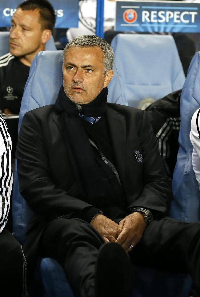 Chelsea's manager Jose Mourinho, centre sits in the technical area as he waits for the Champions League group E soccer match between Chelsea and Basel to begin at Stamford Bridge stadium in London, Wednesday, Sept. 18, 2013