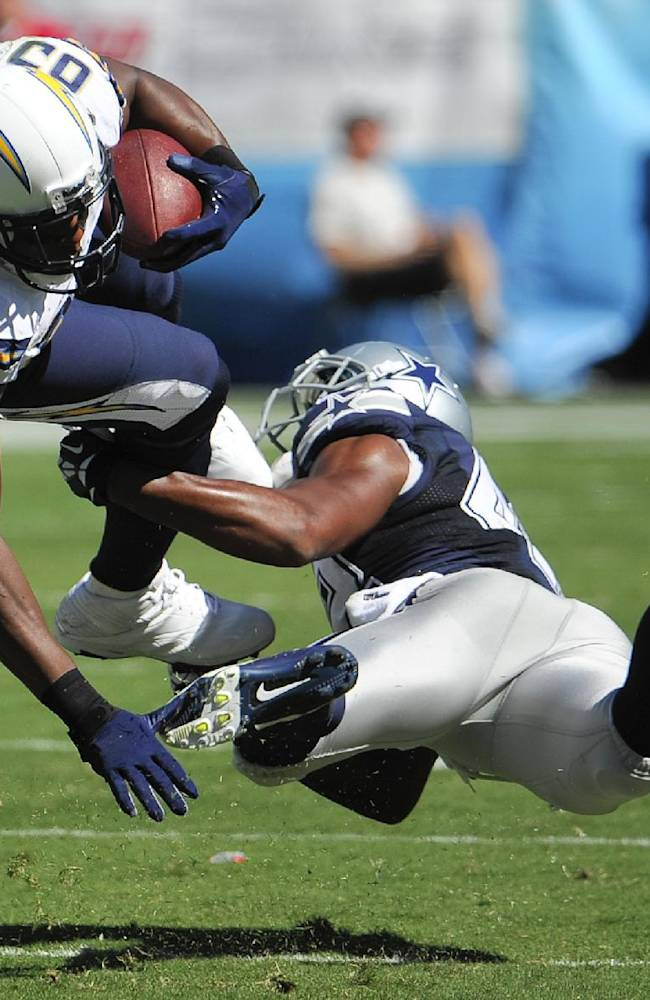 Dallas Cowboys free safety Barry Church, right, tackles San Diego Chargers tight end Antonio Gates during the first half of an NFL football game Sunday, Sept. 29, 2013, in San Diego