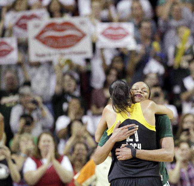 Seattle Storm's Tina Thompson is embraced by Tulsa Shock's Jennifer Lacy as Thompson leaves the game late in the second half of a WNBA basketball game Saturday, Sept. 14, 2013, in Seattle. The Storm won 85-73