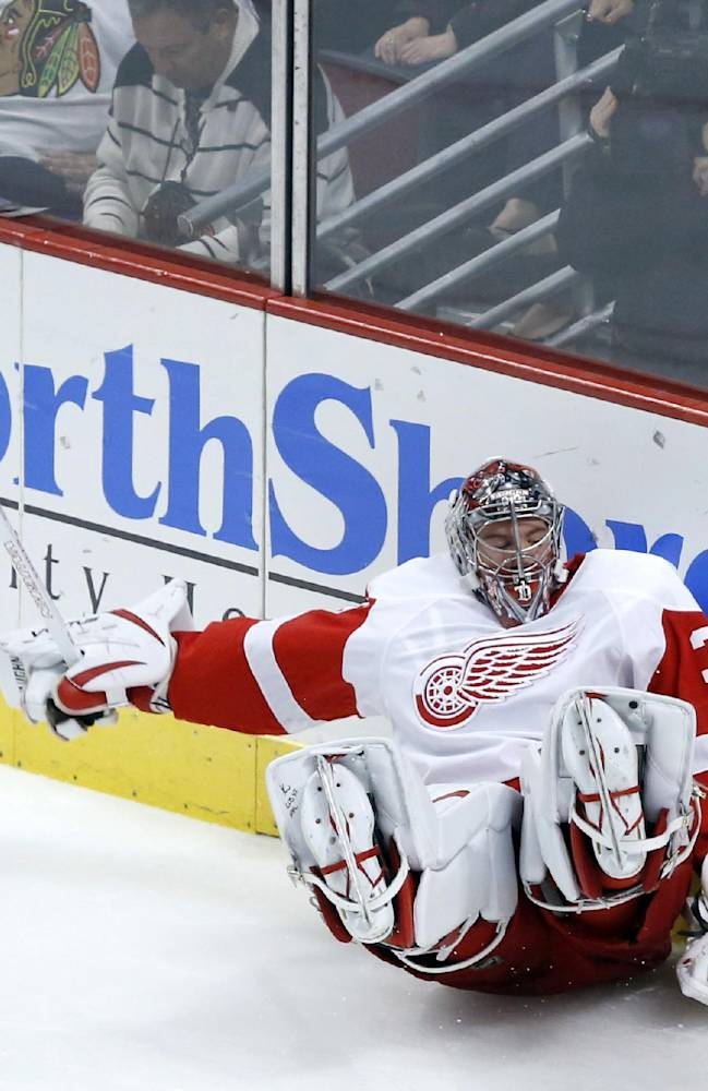 Detroit Red Wings goalie Jared Coreau falls to the ice as he handles a puck behind the net during the third period of an NHL preseason hockey game against the Chicago Blackhawks, Tuesday, Sept. 17, 2013, in Chicago. The Blackhawks won 2-0