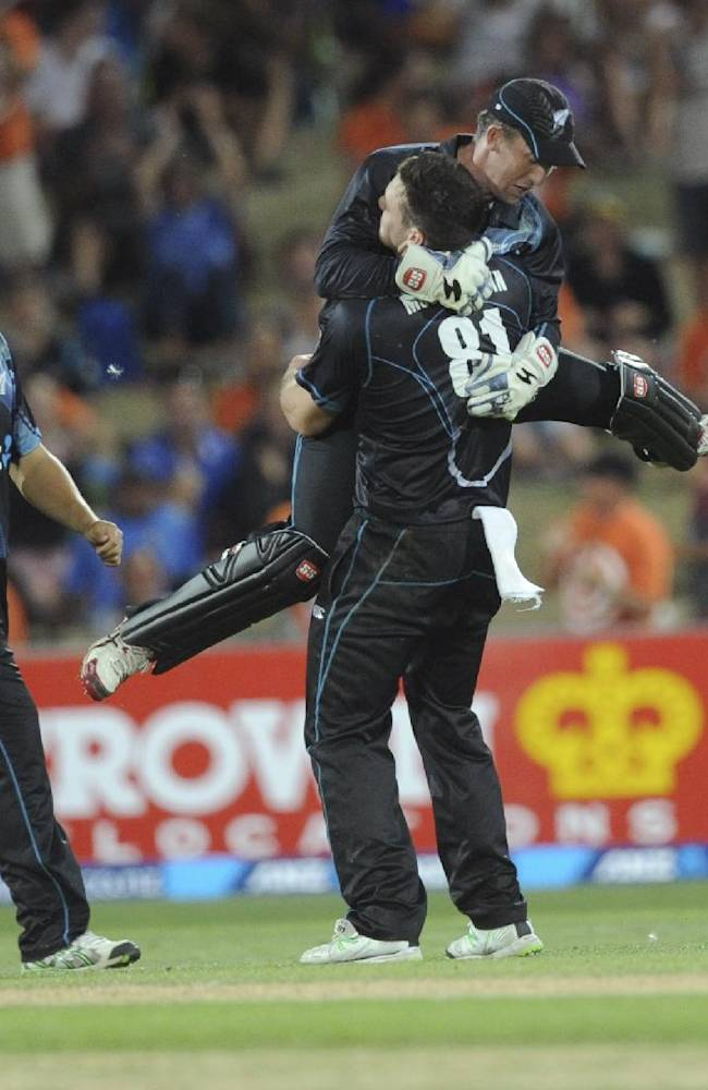 New Zealand's Mitchell McClenaghan hugs teammate Luke Ronchi after he took the catch off his bowling to dismiss India's MS Dhoni for 40 in their first one day international cricket match at McLean Park in Napier, New Zealand, Sunday, Jan. 19, 2014